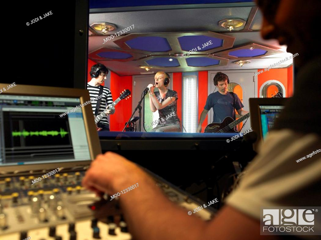 Stock Photo: Band in recording studio technician in foreground.