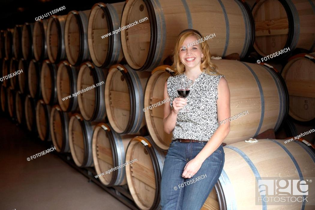 Stock Photo: Woman drinking red wine by wine barrels (portrait).