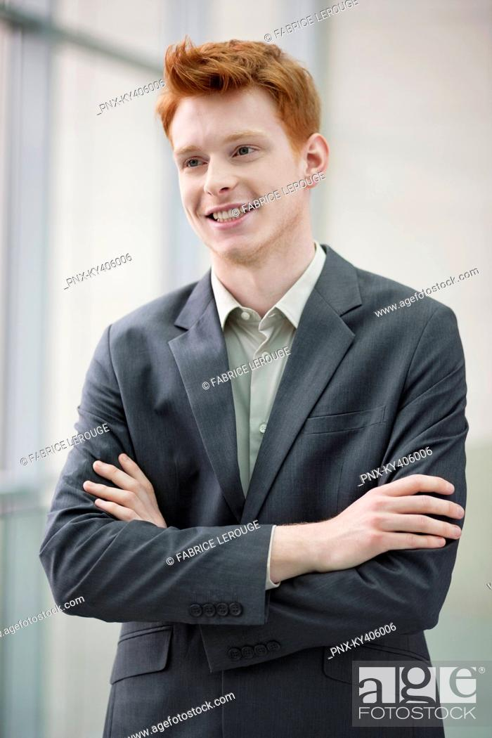 Stock Photo: Close-up of a businessman smiling with his arms crossed in an office.