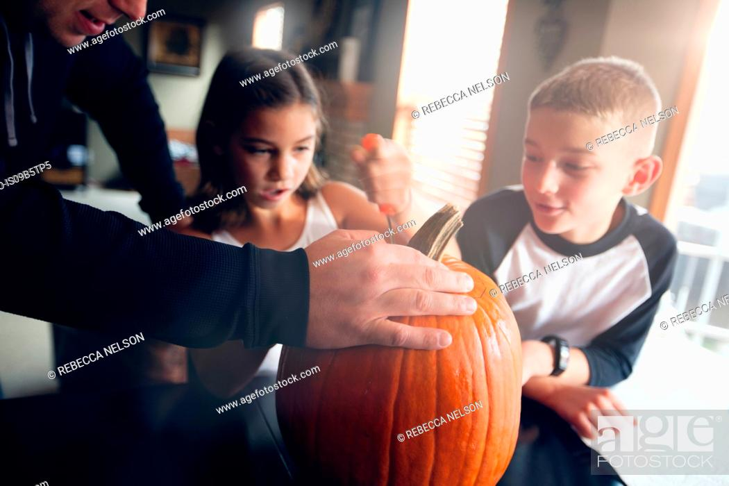Stock Photo: Father and children pumpkin carving.