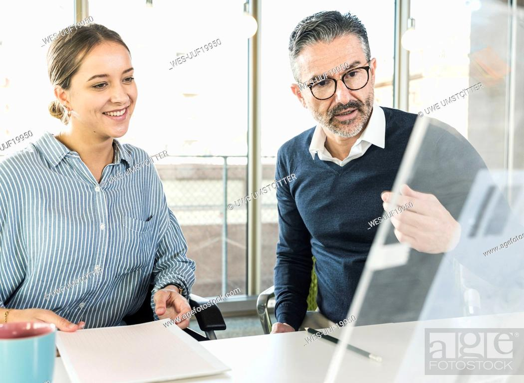 Stock Photo: Mature businessman and young businesswoman talking at desk in office.