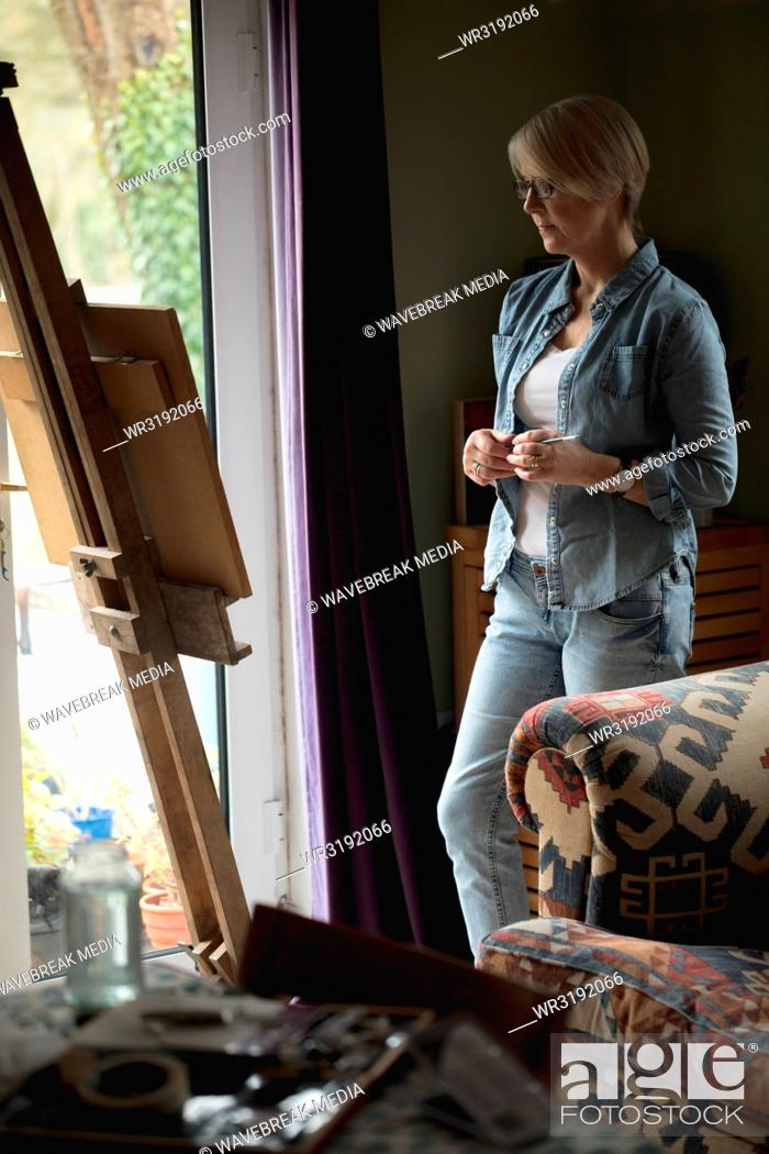 Stock Photo: Female artist observing painting on canvas.