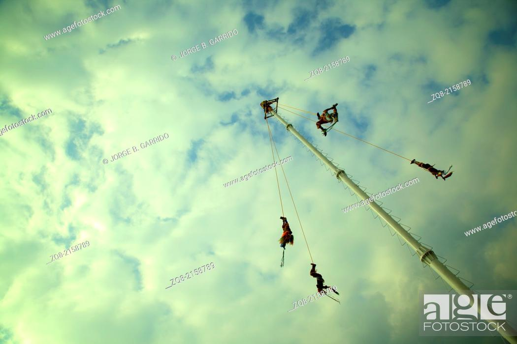"""Stock Photo: Daring men from Papantla Veracruz perform the """"""""Dance of the Flyers"""""""" a ceremony which is classified as intangible cultural heritage by UNESCO, Cumbre Tajín."""