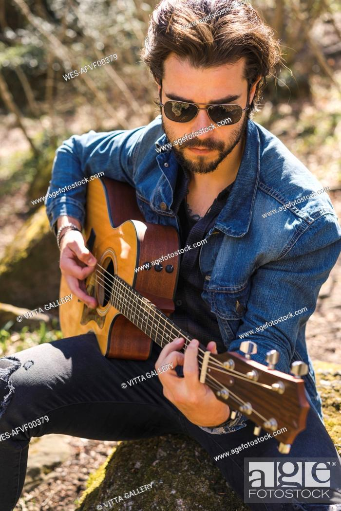 Stock Photo: Young man playing guitar outdoors.