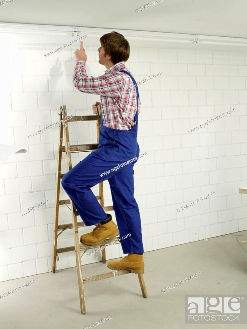 Stock Photo: Man in work wear on a ladder.