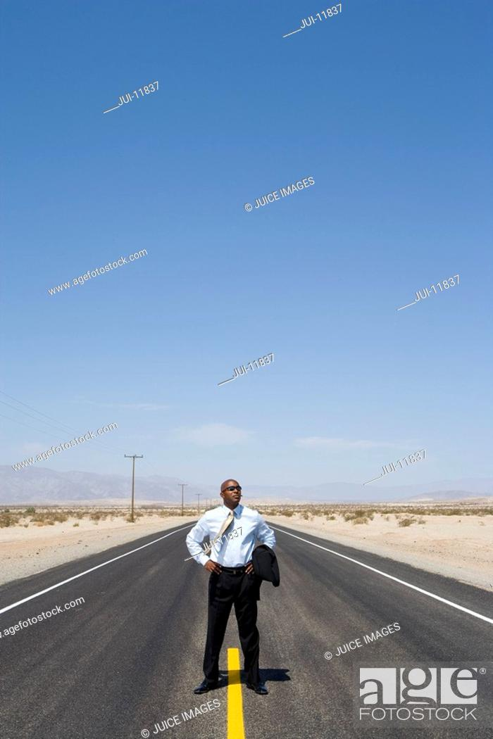 Stock Photo: Businessman on line in middle of road in desert with hands on hips.