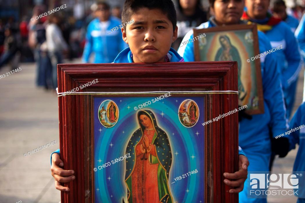 Stock Photo: A young pilgrim holds an image of the Virgin of Guadalupe at the pilgrimage to Our Lady of Guadalupe Basilica in Mexico City, Mexico, December 10, 2013.