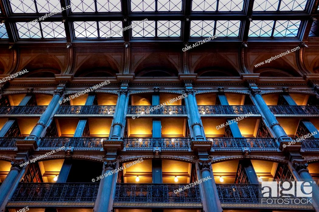 Imagen: A low-angle shot of the levels of the George Peabody Library, a research library for Johns Hopkins University, with cast iron railings and exposed glowing light.