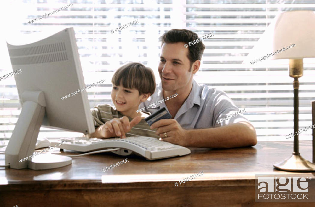 Stock Photo: Father and his son sitting in front of a computer.