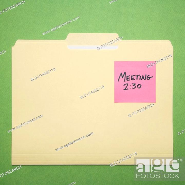 Stock Photo: Folder with pink sticky note reminder for a meeting on a green background.