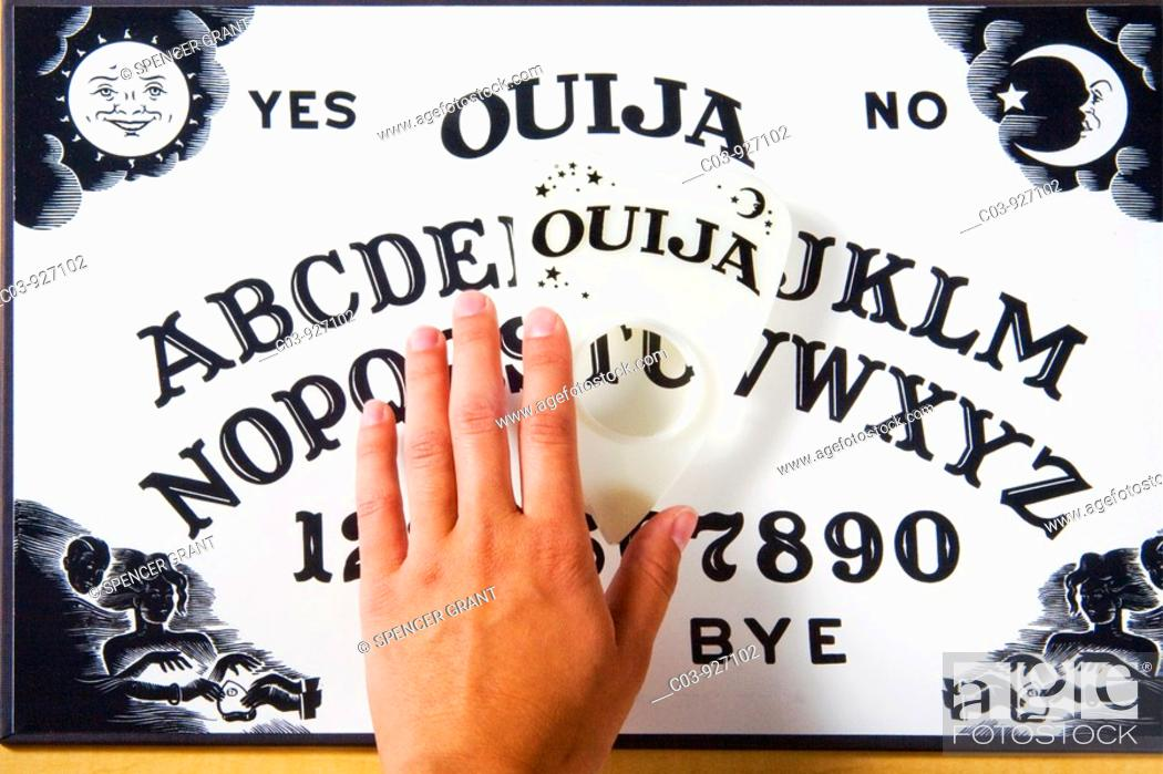The Hand Of A Young Adult Slides The Plaquet Of A Ouija Board A