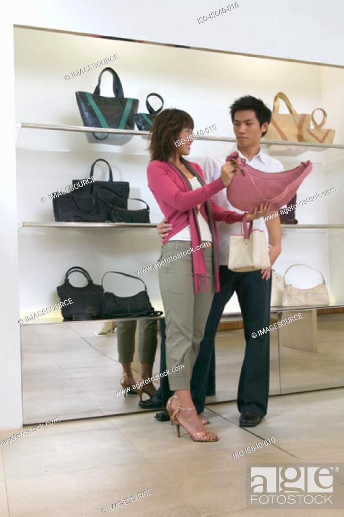 Stock Photo: Couple shopping for handbag.