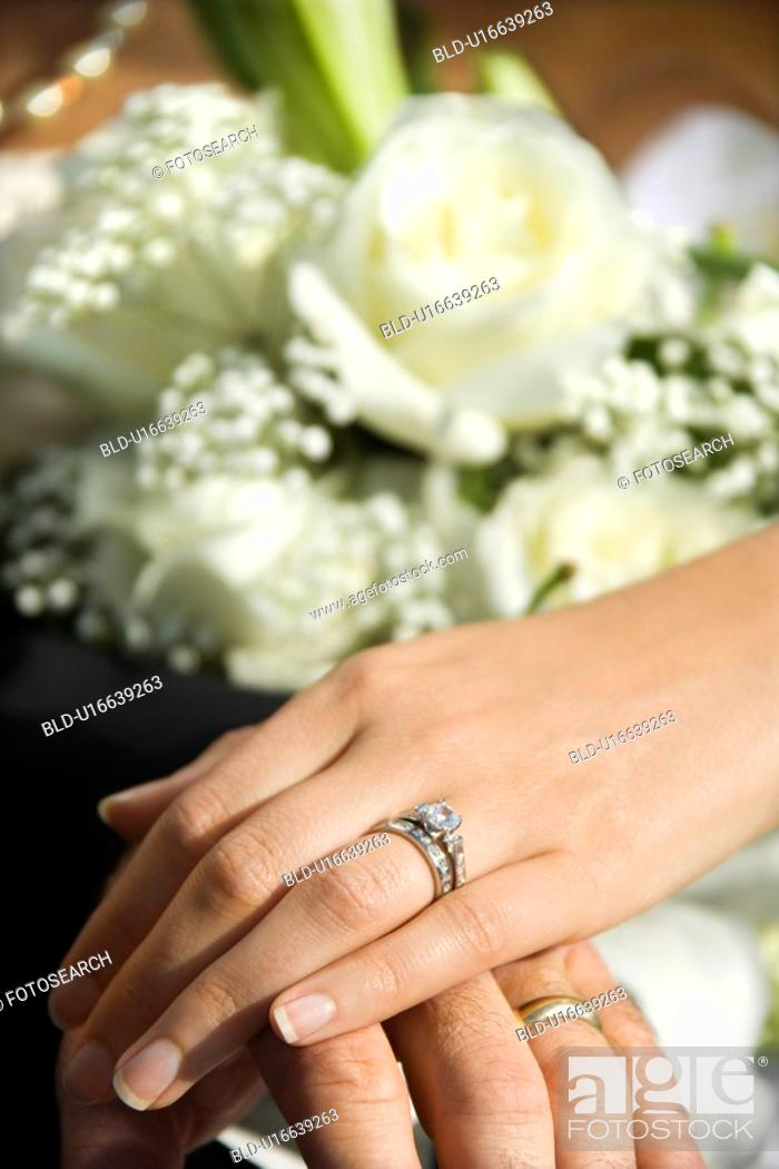 Stock Photo: Caucasian mid-adult male and female hands with wedding rings.