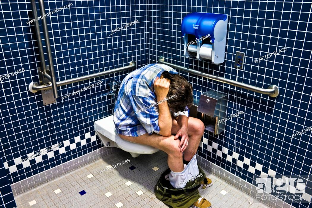 Stock Photo: Man sitting on the toilet in an office building bathroom.