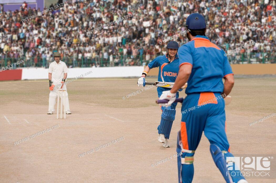 Stock Photo: Two cricket batsmen running between the wicket for run.