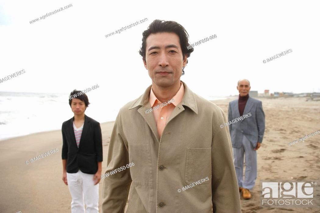 Stock Photo: Mature man smiling while son and father standing in background.