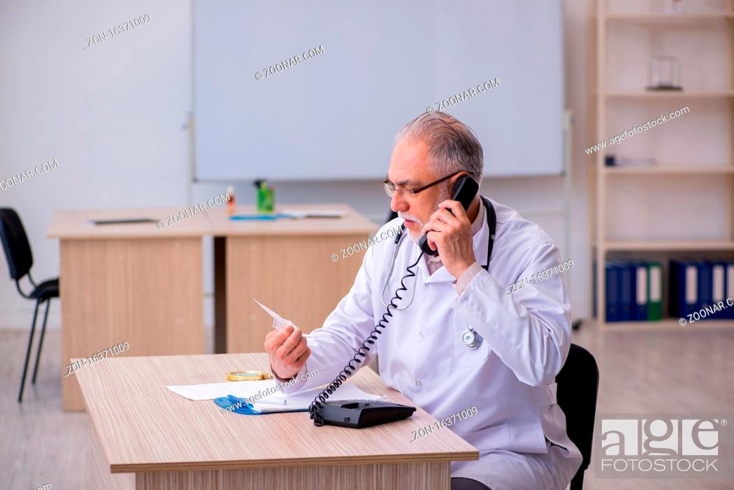 Stock Photo: Old doctor in telemedicine concept.