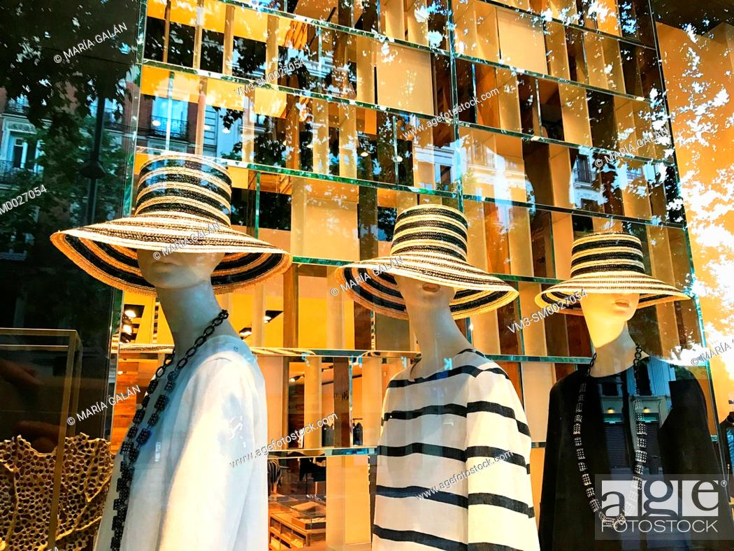 Stock Photo: Three mannequins wearing hat in a shop window. Serrano street, Madrid, Spain.