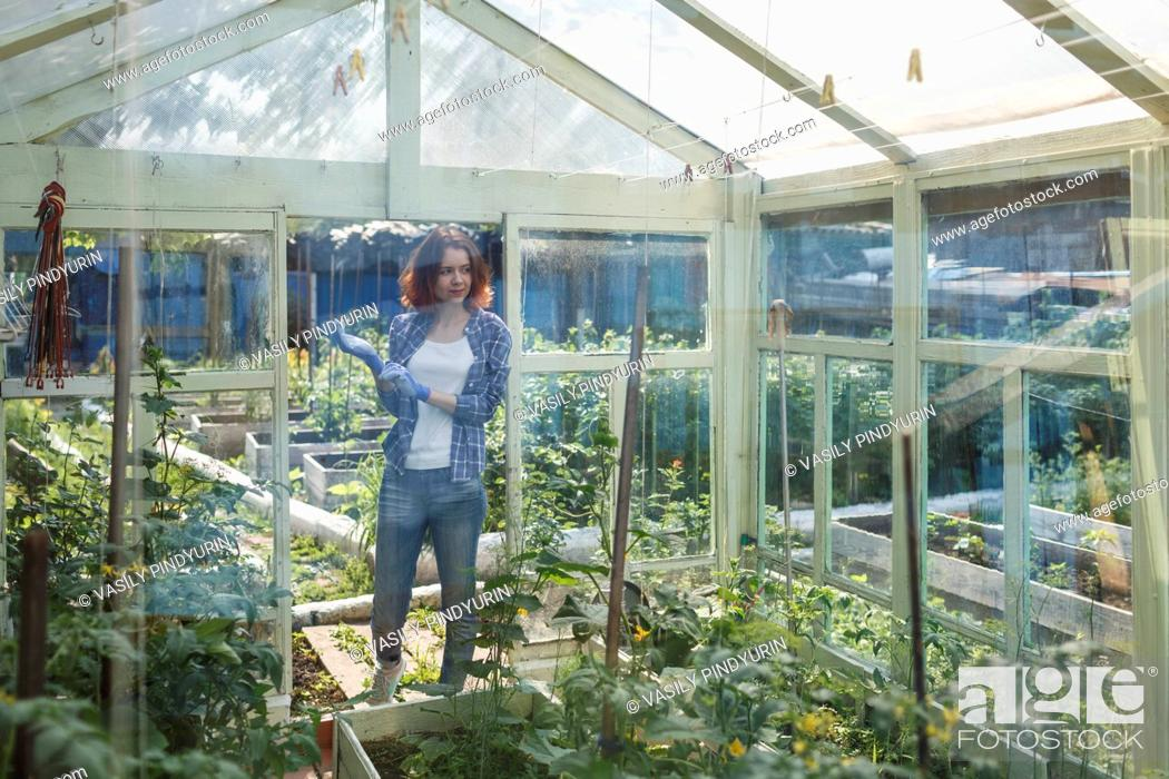 Stock Photo: Smiling young woman standing in a greenhouse.