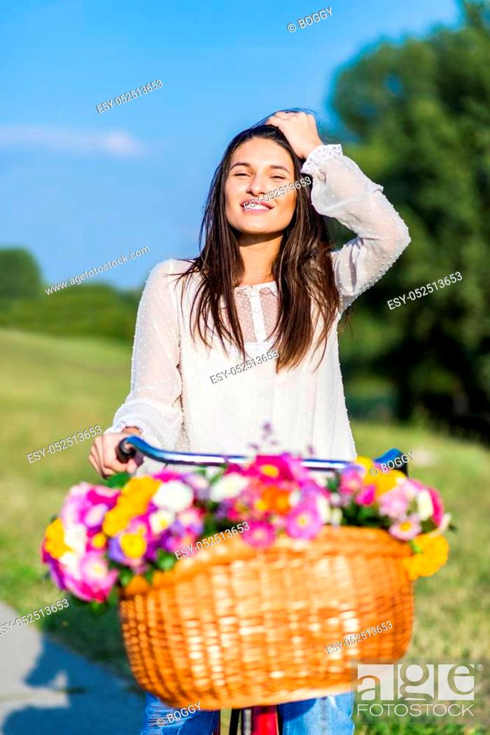 Stock Photo: Young girl rides a bicycle with a basket full of flowers.