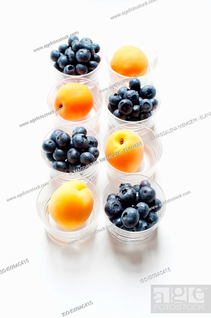 Stock Photo: Still life with rows of apricots and blueberries in glass tumblers.