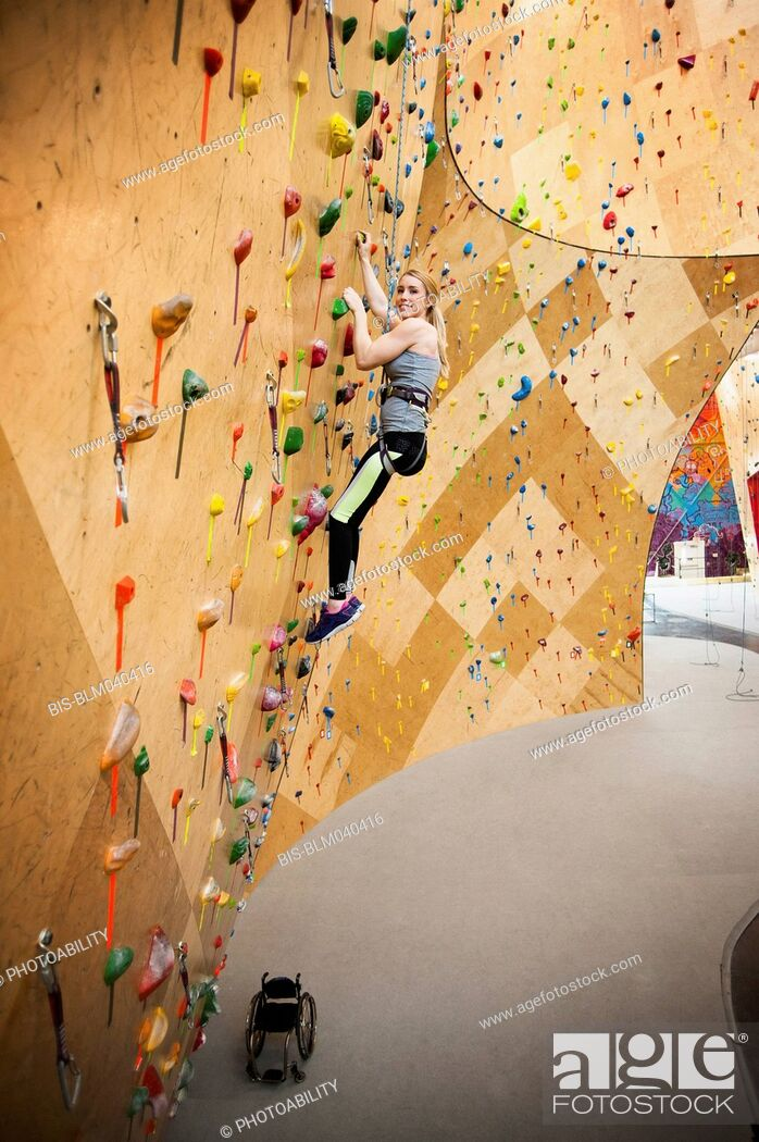 Stock Photo: Paraplegic woman rock climbing in gym.