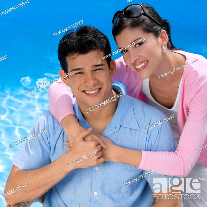 Stock Photo: Portrait of a young couple smiling at the poolside.