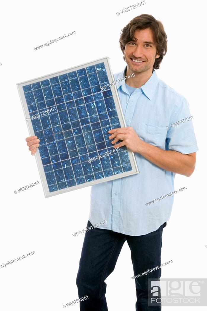 Stock Photo: Man holding solar panel.