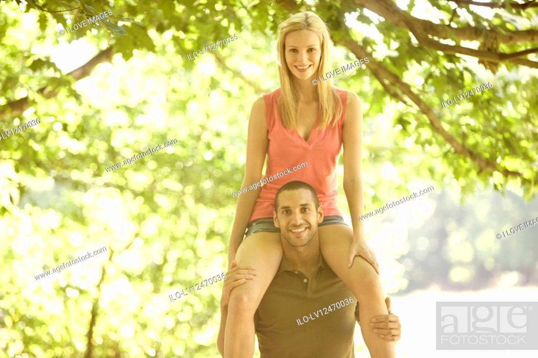 Stock Photo: A young man carrying his girlfriend on shoulders, smiling.