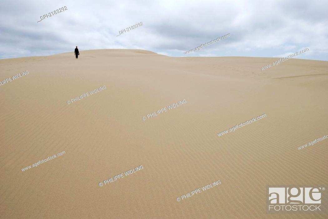 Imagen: A Woman Walking Alone On A Sand Dune In The Distance, Florence Oregon United States Of America.
