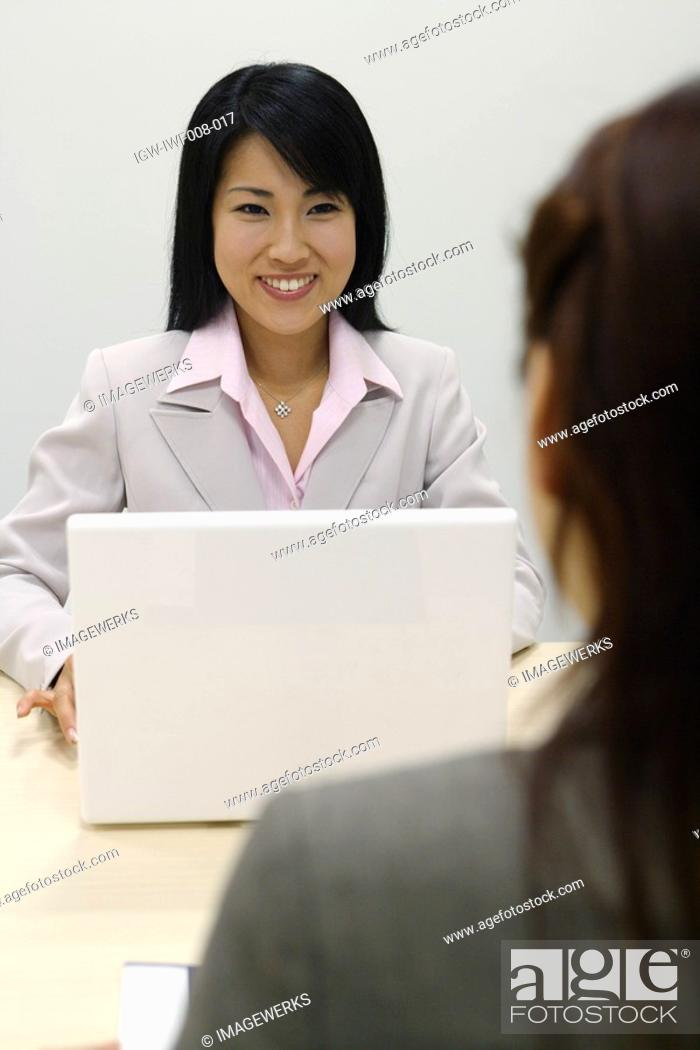 Stock Photo: A woman working on her laptop smiles at her colleague.