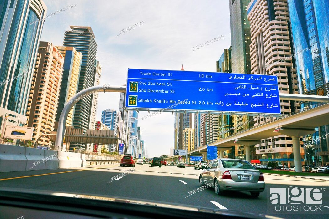 Stock Photo: City of Dubai. Road signs driving along city centre Sheikh Zayed Road. Al Yaquob Tower in distance. United Arab Emirates.
