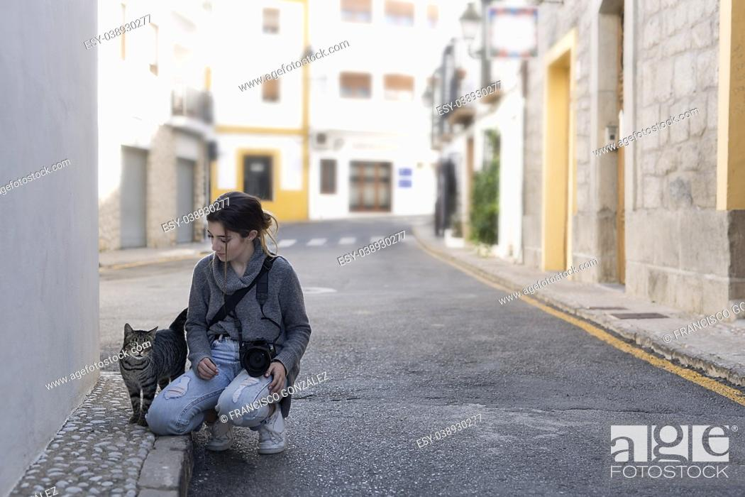 Photo de stock: Teenage girl with her photo camera greeting a street cat in the town of Altea, in the province of Alicante, Spain.
