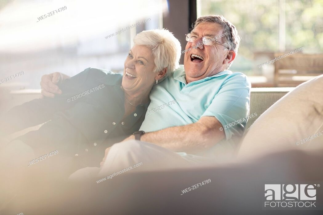 Stock Photo: Happy senior couple on couch at home.