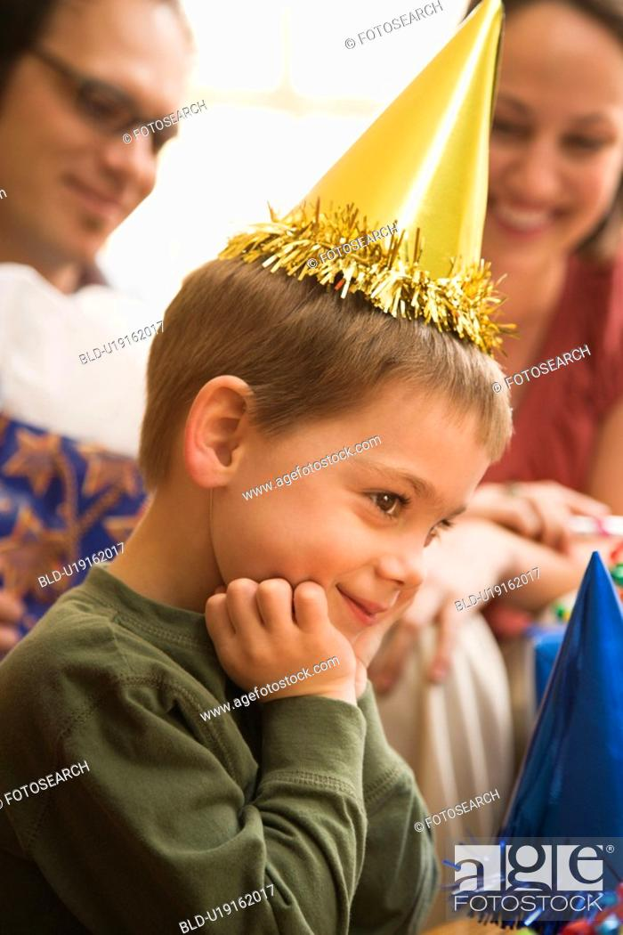 Stock Photo: Boy at birthday party looking to the side and smiling.
