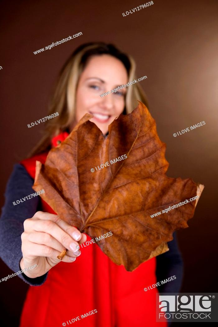 Stock Photo: A mid adult woman holding a dried leaf, smiling.