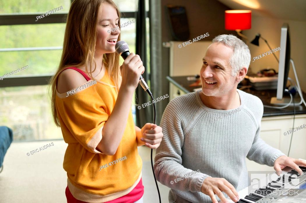Stock Photo: Man playing a piano with his daughter singing.