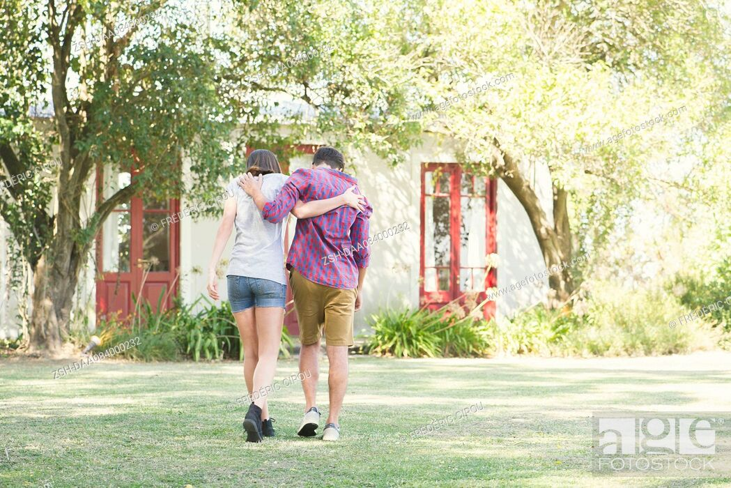 Stock Photo: Couple walking outdoors with arms around each other's shoulders, rear view.