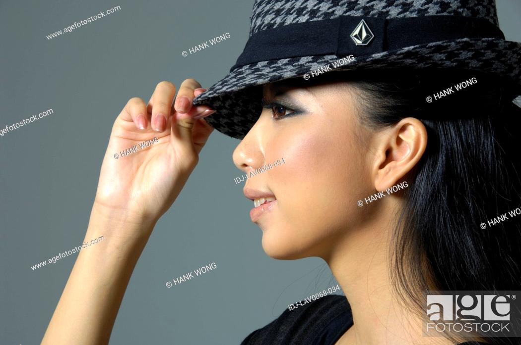 Stock Photo: Close-up of a fashion model holding her hat.