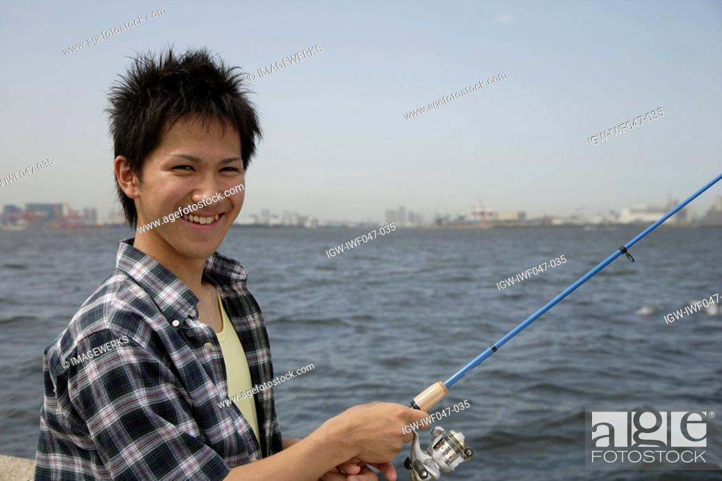 Stock Photo: Portrait of a young man holding a fishing rod.