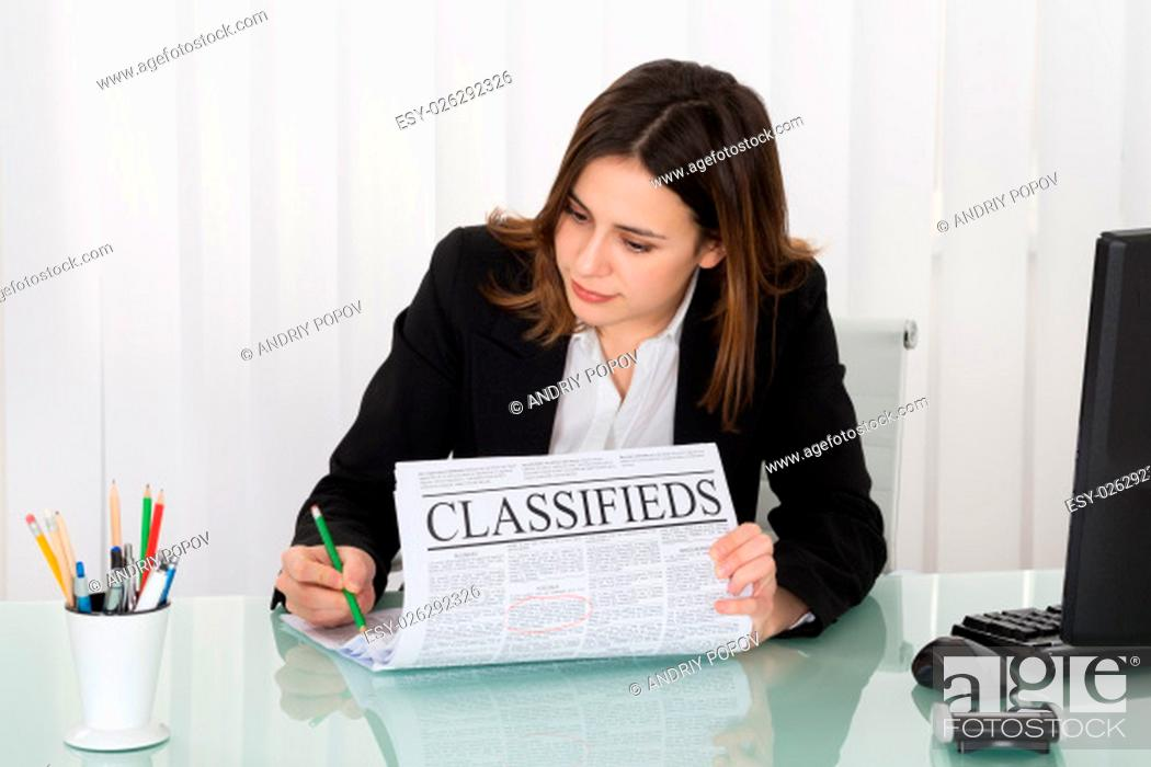 Stock Photo: Young Businesswoman Highlighting Advertisement On Newspaper In Office.