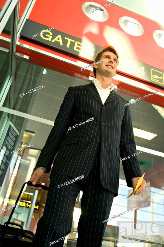 Stock Photo: Low angle view of a businessman walking with his luggage at an airport.
