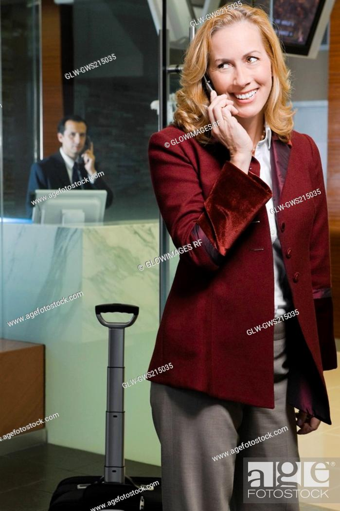 Stock Photo: Mature woman talking on a mobile phone and smiling.