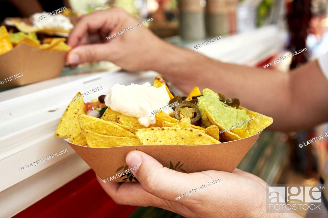 Stock Photo: Tortilla chips with sour cream and guacamole at a market (Barcelona, Spain).
