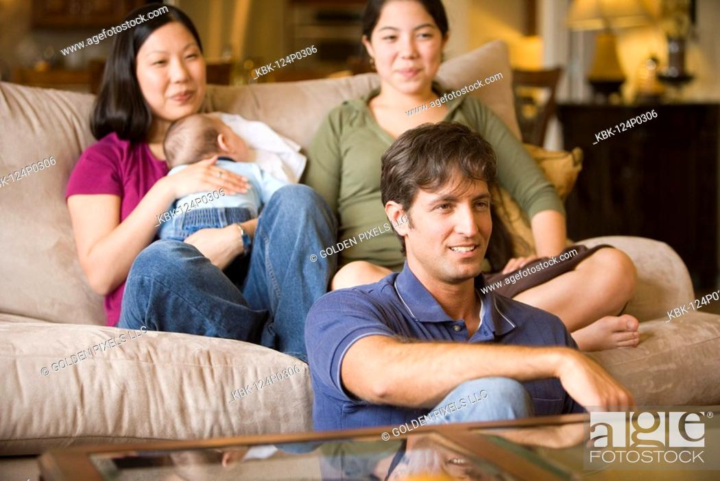 Imagen: Portrait of an Asian-Caucasian family sitting on sofa and the floor.