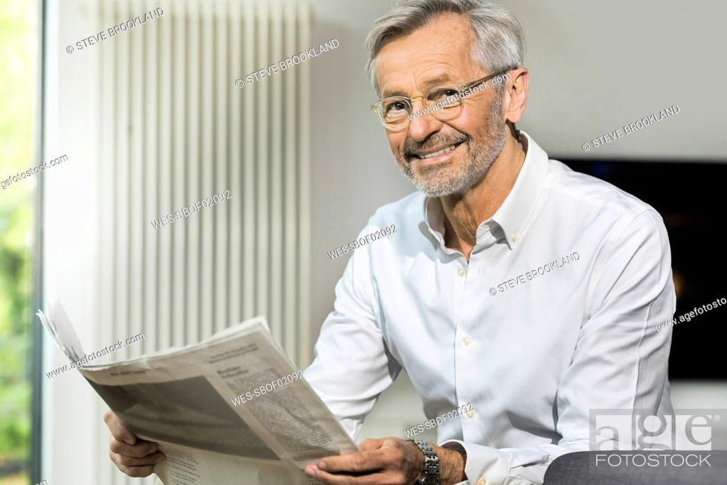Stock Photo: Portait of smiling senior man with grey hair in modern design living room reading newspaper.