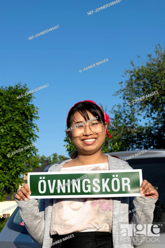 Stock Photo: Female student driver holding sign.
