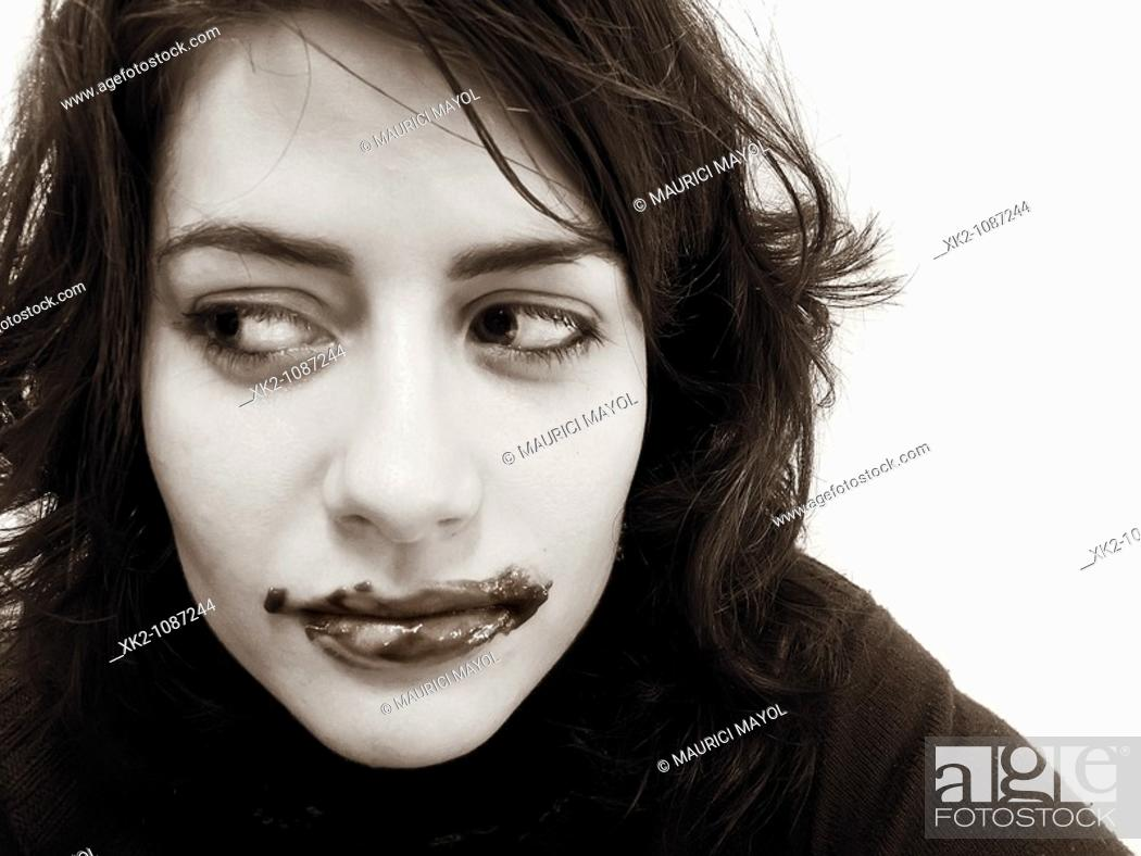 Stock Photo: Portrait of woman with guilty expression and chocolate around her mouth.