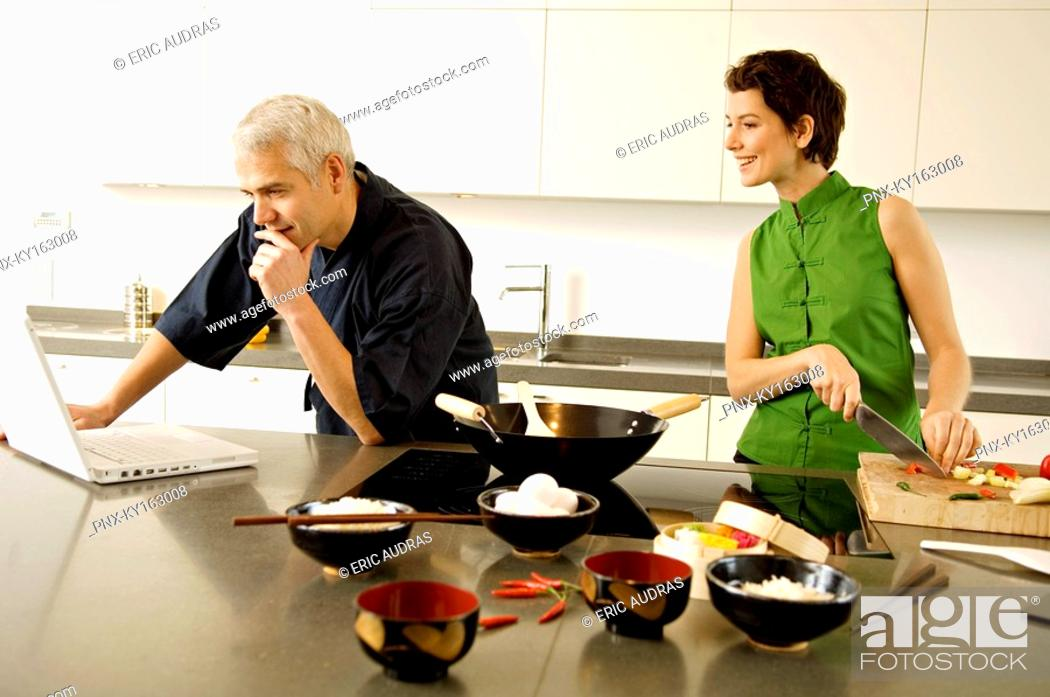 Stock Photo: Mature man using a laptop with a mid adult woman chopping vegetables in the kitchen.