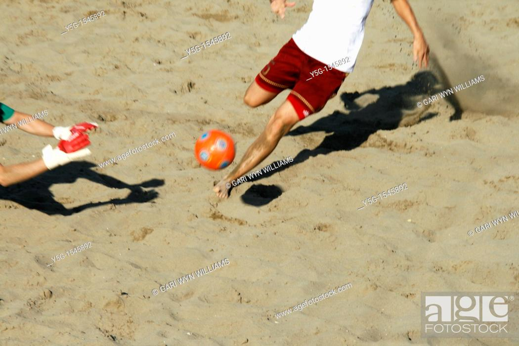 Stock Photo: players in action at a beach soccer tournament.